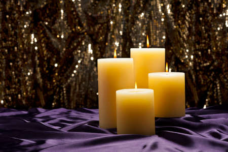 Four candles over purple velvet, with gold glitter background photo