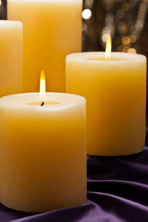 lit candle: Four candles over purple velvet, with gold glitter background Stock Photo