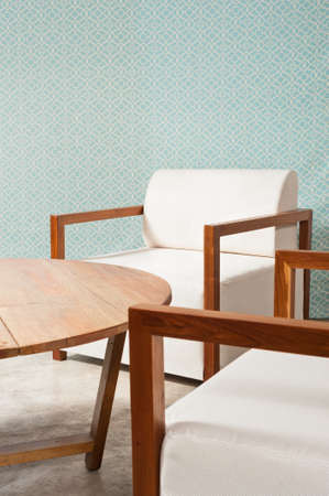 Brown white furniture in a living room and turquoise blue wallpaper photo