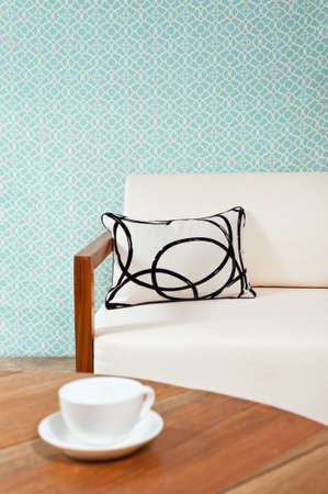 Bright white furniture in a living room with turquoise blue wallpaper photo