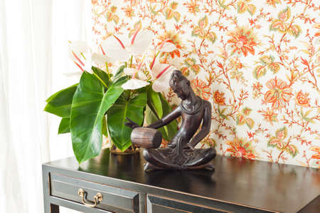 Side table with flowers and interior decoration next to bright window photo
