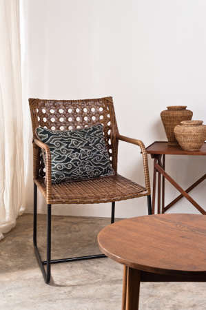Brown rattan Chair in interior setting in front of a white wall photo