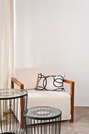Bright white armchair in a living room with metal table
