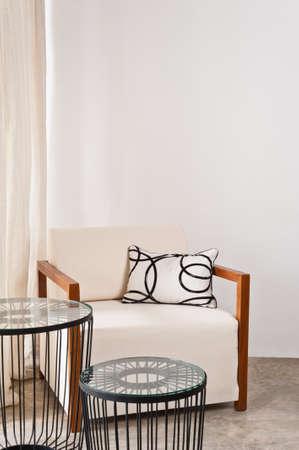 Zářivě bílé křeslo v obývacím pokoji s kovovou tabulkou