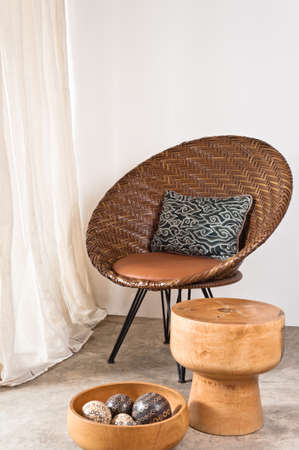 Brown rattan Chair in interior setting in front of a white wall