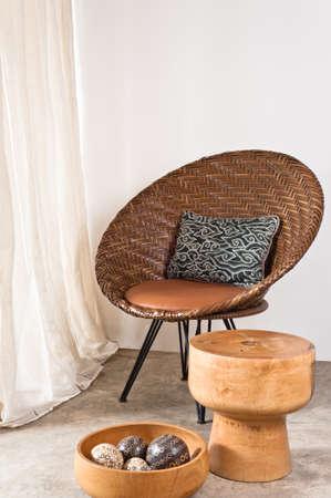 curtain design: Brown rattan sedia in ambiente interno di fronte a un muro bianco Archivio Fotografico