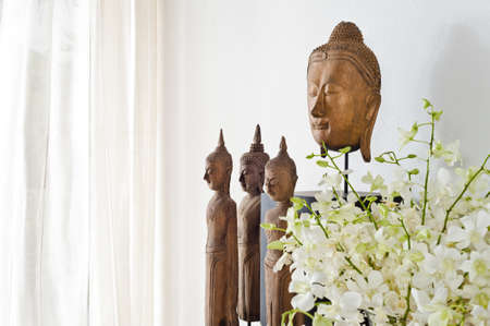 Buddha head and figurine in front of a white wall photo
