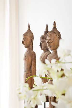 white room: Buddha figurine in front of a white wall Stock Photo