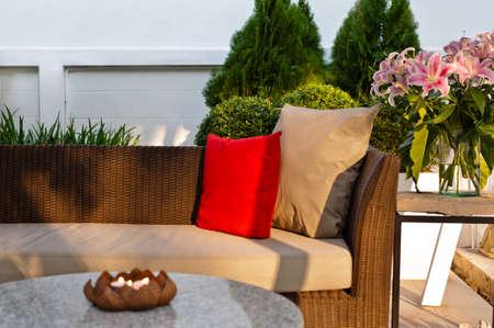 Venkovní terasa k posezení s pěkným ratan sedací soupravou při západu slunce