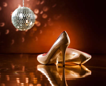 Beautiful brown stilettos on the dance floor with mirror ball Stock Photo