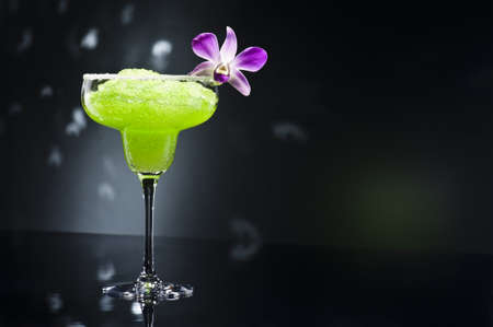 frozen drink:  Green margarita cocktail with orchid flower Stock Photo