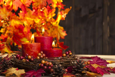 Candles in nice and beautiful colorful autumn leaves photo