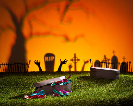 Halloween coffin on lawn with sweets and candies photo