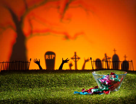 horrific: Zombie hands of a graveyard catching the sweets Stock Photo