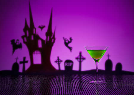 Green Martini in Halloween setting with witch and haunted house photo