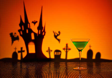 Green Martini in Halloween setting with a haunted house photo