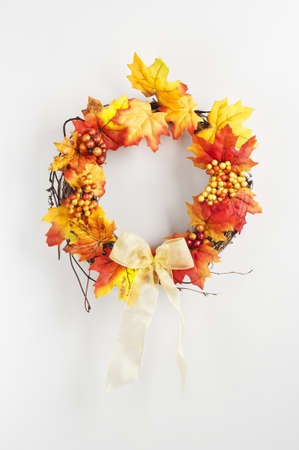 Autumn wreath hanging on a bright door photo