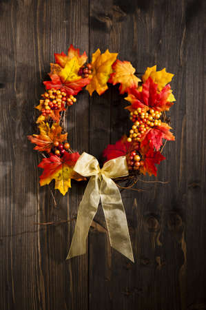 Autumn wreath hanging on a wooden door photo