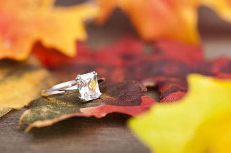 anillo de compromiso: Anillo de compromiso de diamantes en la decoración festiva de otoño