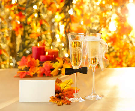 Glasses of champagne and candles: Champagne glasses with conceptual heterosexual decoration for straight couples with place card