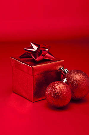 Red bauble and present in red Christmas setting photo