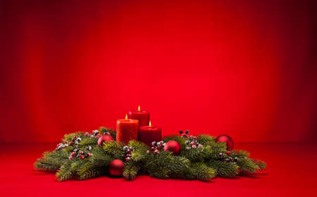 Red advent flower arangement with burning candles