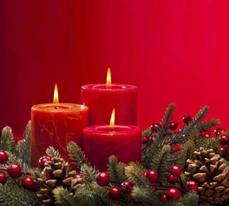 Red advent flower arangement with burning candles photo