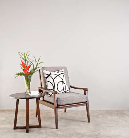 red chair: Grey upholstered chair in living room with flowers