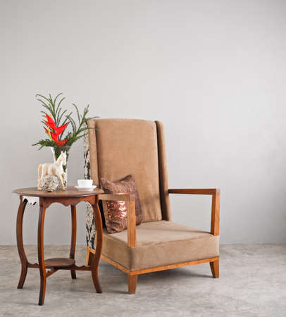 side table: Beige upholstered chair with side table and flowers