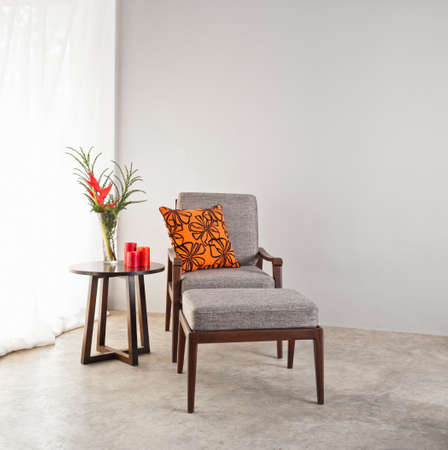 the footstool: Grey upholstered chair with footstool and orange pillow