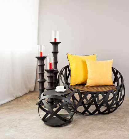 home  lighting: Metal sofa with yellow pillow and candles Stock Photo
