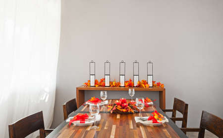 Dinner table setting in warm orange red autumn colors photo