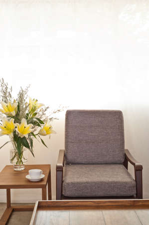 Grey upholstered chair in flower setting infront of white curtain photo