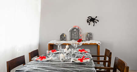 Halloween dinner table setup with decoration on the side board photo