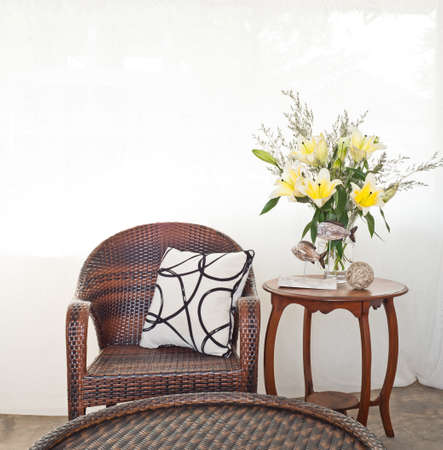 Outdoor chair in flower setting in front of white curtain photo
