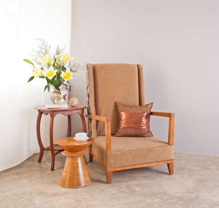 upholstered: Beige upholstered chair in interior setting and coffee cup