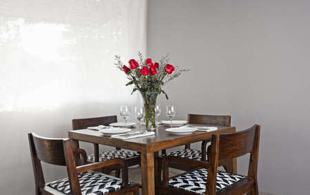 dinning table: Dinner table setup for four with red roses Stock Photo