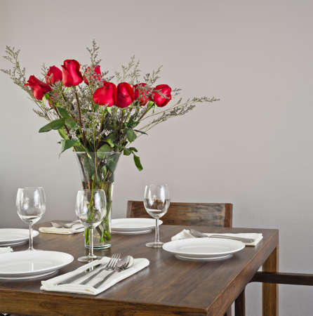 Dinner table setup for four with red roses photo
