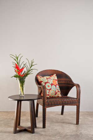 seater: Basket weaved seater chair with flower in a vase
