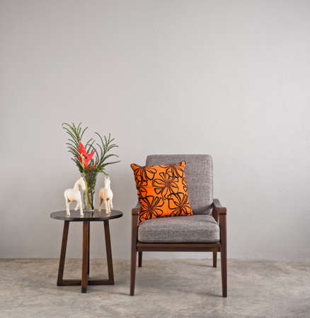 Grey upholstered chair in living room with flowers Standard-Bild