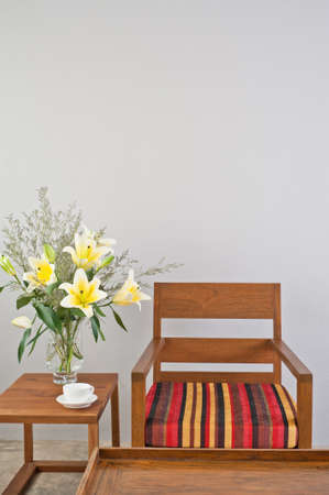 Colorful upholstered chair with side table and flowers photo