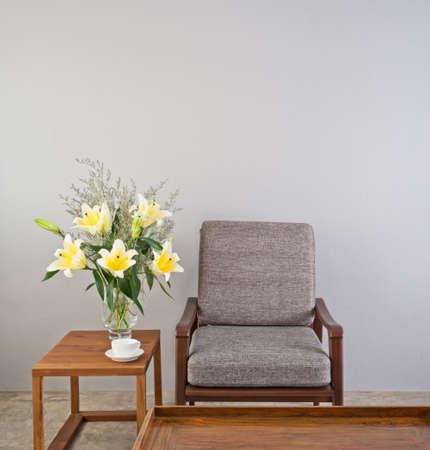 Beige Polstersessel mit Beistelltisch und Blumen