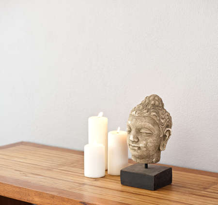 Buddha head with candes in front of a grey wall photo