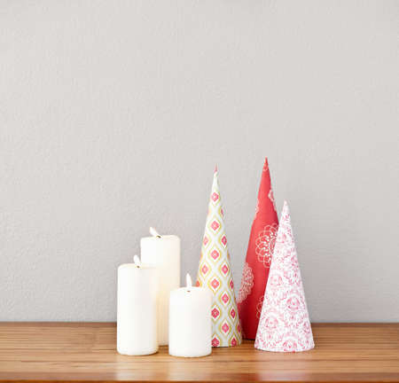 Paper cones and lit candles on a side board as deco photo