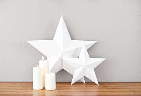 aparador: Estrelas e velas acesas em uma placa de lado como deco Imagens