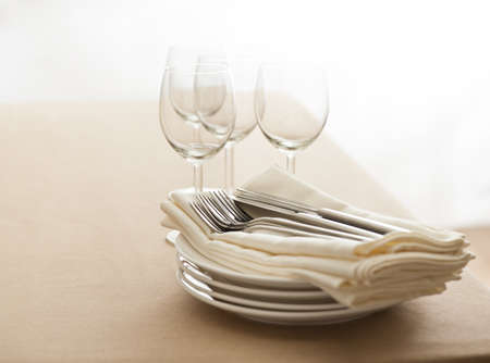 Wine glasses, cutlery, plates and napkins on a table photo