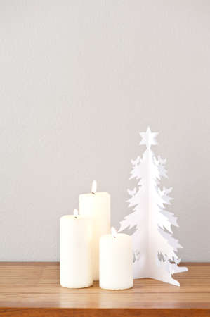 Paper Christmas tree and candles on a side board photo