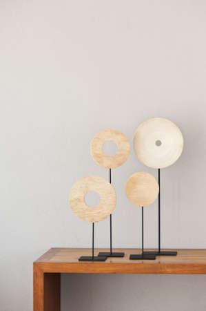 Round wooden interior decoration on beige brown side board Stock Photo