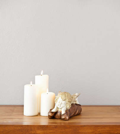 Angel and white candles on side board