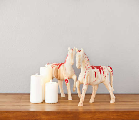 Horses decoration and white candles on side board photo